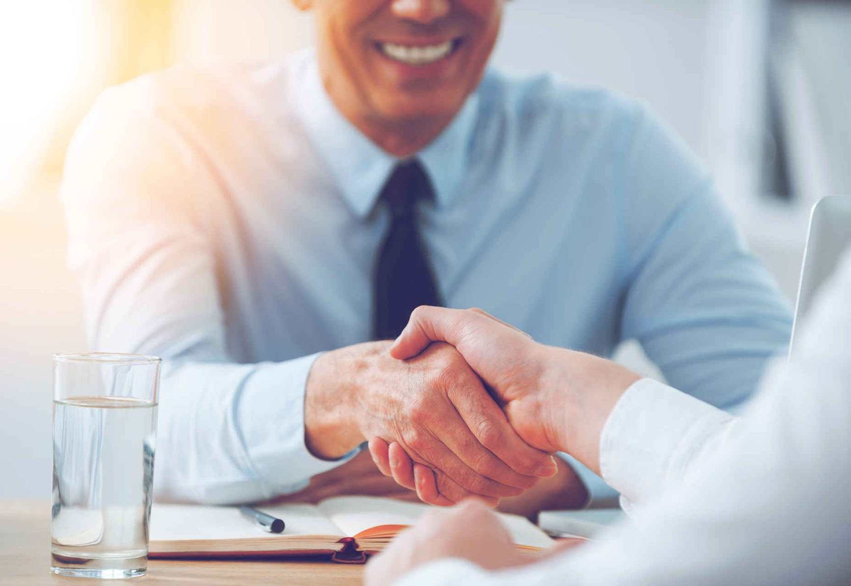 Good deal. Close-up of two business people shaking hands while sitting at the working place